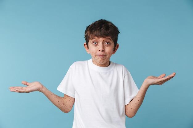 Portret zbliżenie zaintrygowany piękny chłopiec z piegami na sobie białą koszulkę na co dzień patrząc z przodu na białym tle nad niebieską ścianą