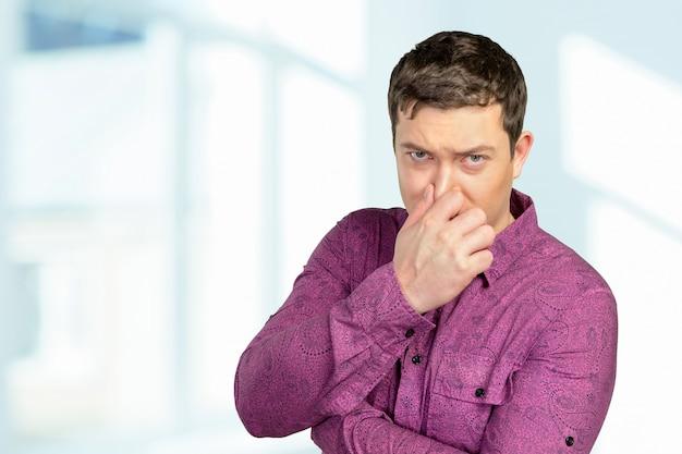 Portret zdegustowanego mężczyzny szczypie nos palcami
