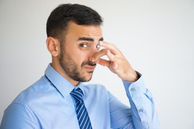 Portret zdegustowany urzędnik szczypanie nos