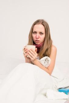 Portret zdenerwowana chora kobieta z grypą, trzymając kubek gorącej herbaty