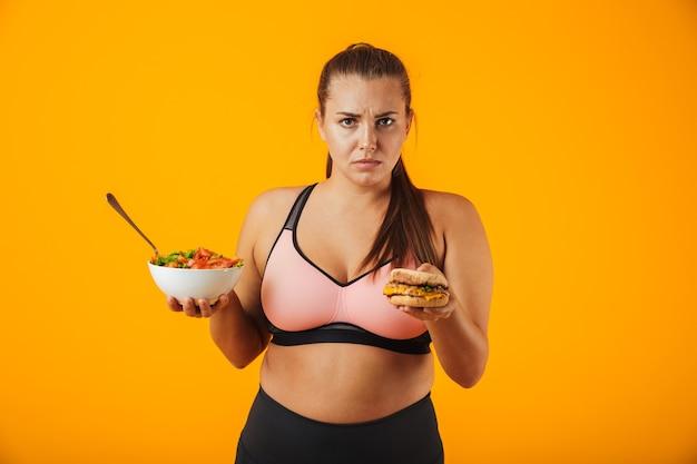 Portret zdenerwowana kobieta fitness z nadwagą noszenie odzieży sportowej stojącej na białym tle nad żółtą ścianą, trzymając miskę z sałatką i burger
