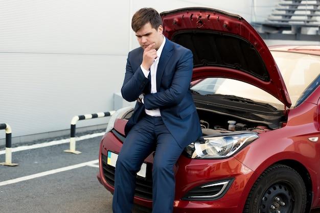 Portret zdenerwowanego biznesmena siedzącego na masce zepsutego samochodu