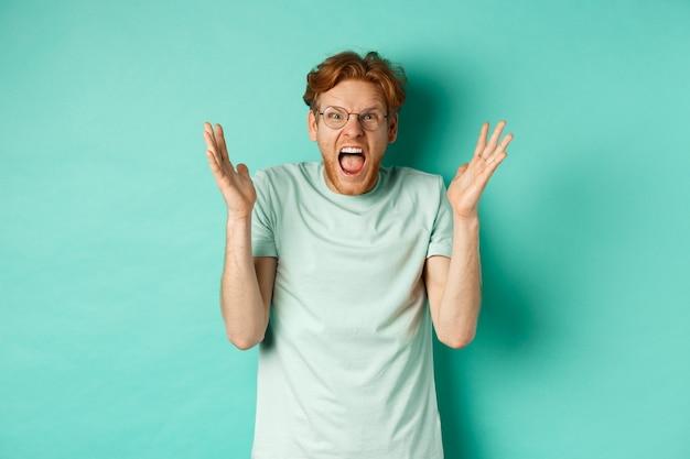 Portret zdenerwowanego i wściekłego rudego faceta tracącego panowanie nad sobą, krzyczącego i ściskającego oburzone ręce, wpatrującego się z wściekłą twarzą w kamerę, stojącego na miętowym tle.