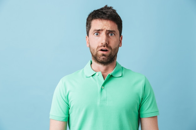Portret zdenerwowanego, zmęczonego, przystojnego brodatego mężczyzny, noszącego zwykłą odzież, stojącego na białym tle nad niebieską ścianą