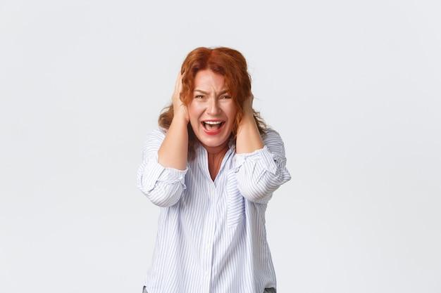 Portret zdenerwowanej i zdenerwowanej rudowłosej kobiety w koszuli, krzyczącej w panice, zakrywającej uszy zaniepokojonymi rękami, stojącej niespokojnie i niepewnie na białym tle. matka panikuje.