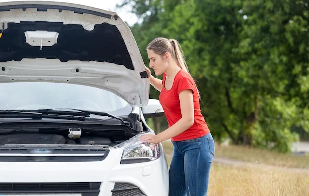 Portret zdenerwowanej kobiety patrzącej pod maskę przegrzanego samochodu w polu