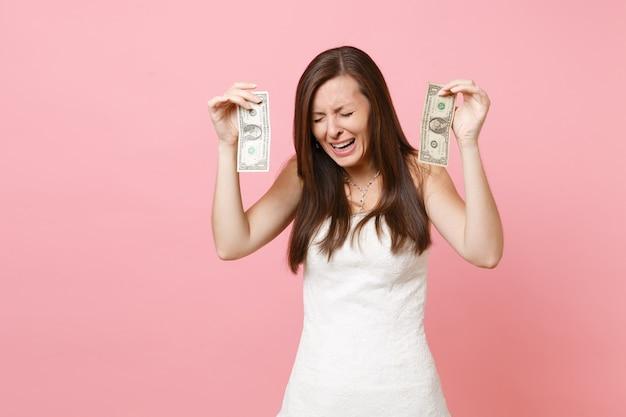 Portret zdenerwowanej smutnej kobiety w białej sukni, płaczącej i trzymającej jednodolarowe banknoty