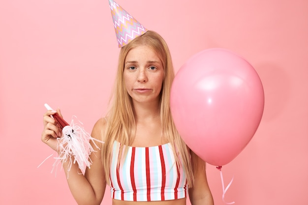 Portret zdenerwowanej, stylowej młodej kobiety rasy kaukaskiej noszącej pasiastą górę i stożkowy kapelusz trzymający balon z helem, rozczarowana znudzonym wyrazem twarzy, smutna i samotna