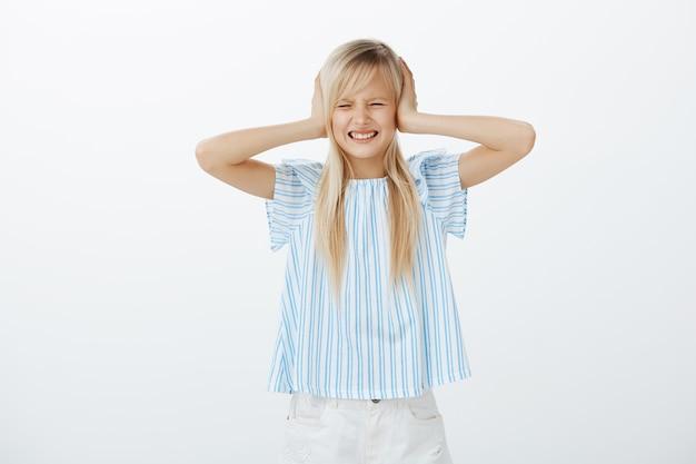 Portret zdenerwowanej, zmęczonej młodej dziewczyny o jasnych włosach, krzywiącej się z niechęci, zakrywającej uszy dłońmi, rozproszonej i zirytowanej głośnym hałasem z ulicy