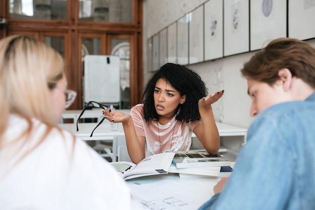 Portret zdenerwowany african american girl z ciemnymi kręconymi włosami siedzi w bibliotece z książkami na stole i emocjonalnie dyskutuje o czymś z przyjaciółmi