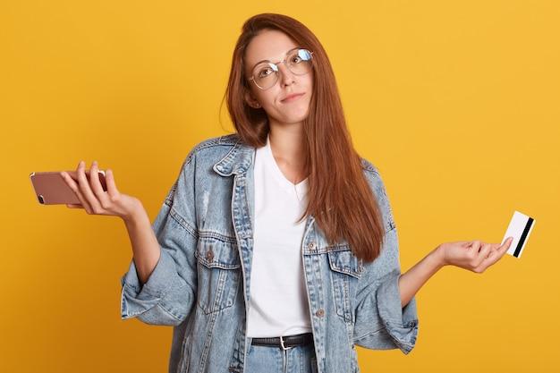 Portret zdenerwowany młoda kobieta nosi dżinsową kurtkę i okulary, rozprzestrzenia ręce, trzyma kartę kredytową i telefon komórkowy, odizolowane na żółtej ścianie. ludzie styl życia i zakupy online.