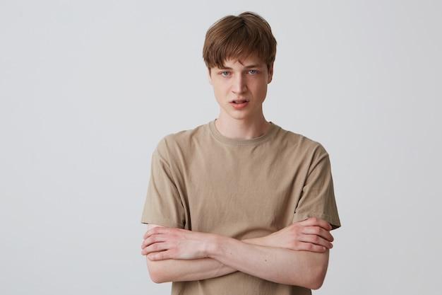 Portret zdenerwowany nieszczęśliwy młody człowiek z krótką fryzurą w beżowej koszulce wygląda rozpaczliwie