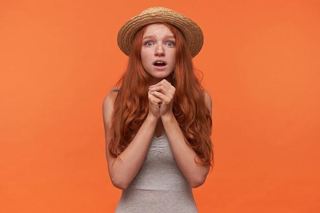 Portret zdesperowanej młodej rudowłosej londyńskiej kobiety w szarej koszuli i kapeluszu, patrząc na kamerę z podniesionymi rękami, mając nadzieję na rozwiązanie jej problemów, odizolowane na pomarańczowym tle