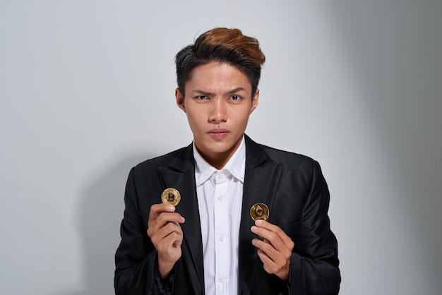 Portret zdezorientowanego dojrzałego biznesmena ubranego w garnitur, trzymającego dwa złote bitcoiny odizolowane na szarym tle
