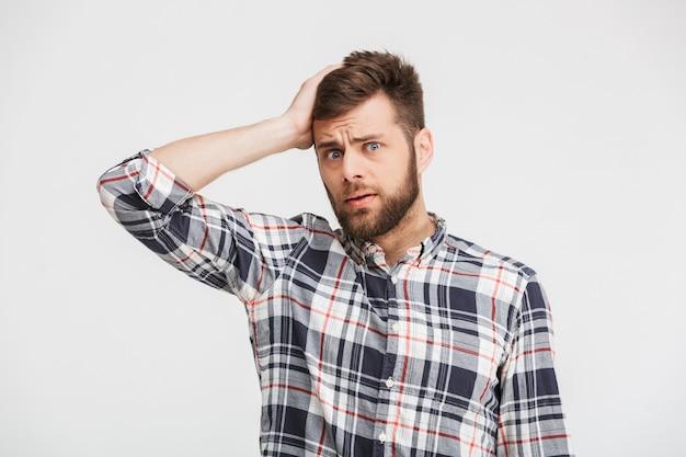 Portret zdezorientowanego młodego człowieka w koszuli w kratę