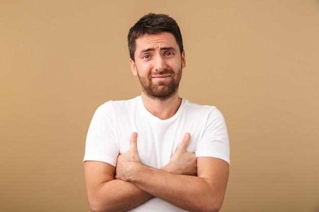 Portret zdezorientowanego młodzieńca ubrany niedbale na białym tle