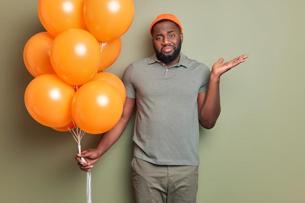 Portret zdezorientowanego, zdziwionego urodzinowego faceta o ciemnej skórze i gęstej brodzie unosi dłoń do góry wygląda niezdecydowany trzyma bukiet pomarańczowych nadmuchanych balonów nie może zdecydować, kogo zaprosić na imprezę ubrany niedbale