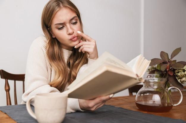 Portret zdezorientowanej kaukaskiej kobiety noszącej zwykłe ubrania, czytającej książkę i pijącej herbatę w przytulnym pokoju