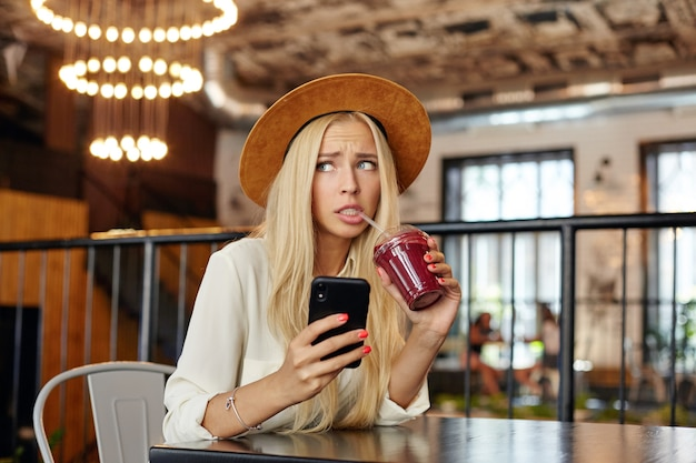 Portret zdezorientowanej młodej blondynki z długimi włosami spoglądającymi na bok i marszczącymi brwiami, trzymając smartfon w dłoni i pijąc smoothie, pozując nad wnętrzem restauracji