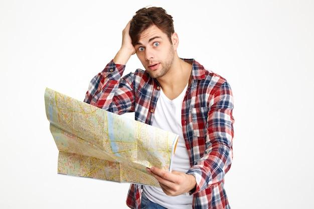 Portret zdezorientowany młody człowiek posiadający mapę podróży