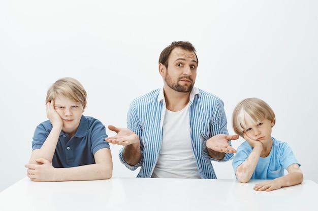 Portret zdezorientowany nieświadomy europejski ojciec siedzi z synami przy stole