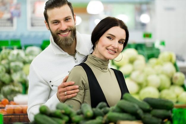 Portret zdrowa para patrzeje owoc i warzywo w supermarkecie podczas gdy robiący zakupy