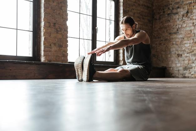 Portret zdrowego sportowca robi ćwiczenia rozciągające