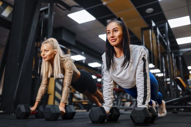 Portret zdrowego stylu życia dwóch młodych dziewcząt sportowych robi deski na siłowni