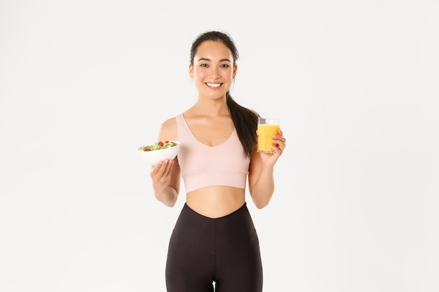 Portret zdrowej i sprawnej, przystojnej azjatyckiej sportsmenki trzymającej sok pomarańczowy i sałatkę, poranne śniadanie przed treningiem