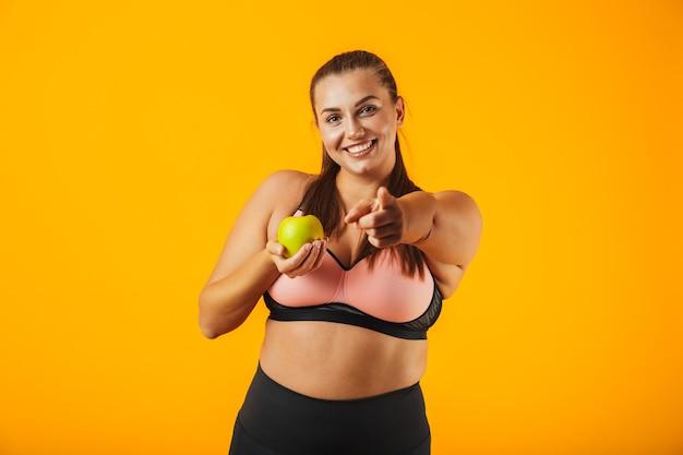 Portret zdrowej kobiety pulchne w stanik sportowy gospodarstwa jabłko, odizolowane na żółtym tle