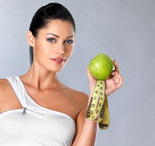 Portret zdrowej kobiety z jabłkiem i butelką wody. zdrowe fitness i jedzenie koncepcja stylu życia.