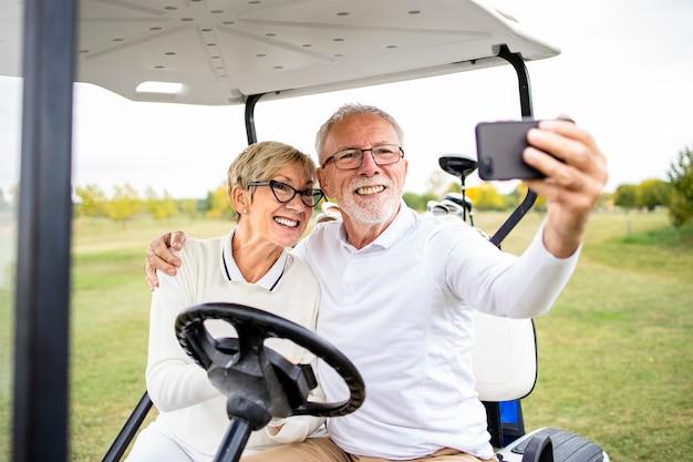 Portret zdrowej pary starszych robienia zdjęć selfie w samochodzie golfowym przed treningiem.