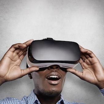 Portret zdumionego ciemnoskórego gracza w zestawie słuchawkowym 3d, który ogląda coś szokującego lub zaskakującego, nie może uwierzyć własnym oczom, z szeroko otwartymi ustami.