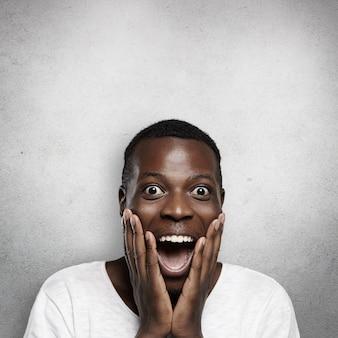 Portret zdumionego młodego afrykańskiego pracownika lub klienta ubranego niedbale, trzymając się za policzki, krzyczącego z zaskoczenia lub zdziwienia, z całkowitym niedowierzaniem, zdumiony, co właśnie zobaczył lub usłyszał