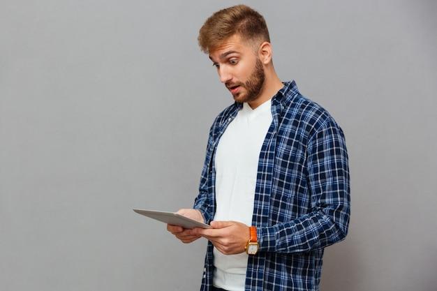 Portret zdumionego przypadkowego mężczyzny korzystającego z komputera typu tablet na szarej ścianie