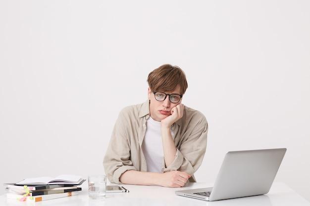 Portret zdumionego studenta młodego mężczyzny w beżowej koszuli wygląda na zaskoczonego i uczy się przy stole z laptopem i notebookami odizolowanymi na białej ścianie
