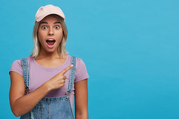 Portret zdumionej blondynki młodej kobiety z otwartymi ustami, ubrana w różową czapkę, fioletową koszulkę i dżinsowy kombinezon, jest zszokowana i wskazuje na bok odizolowany na niebieskiej ścianie