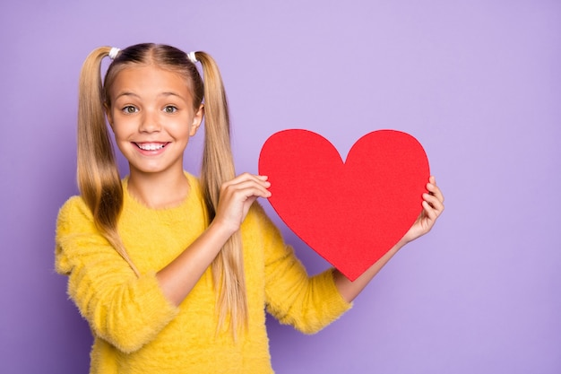 Portret zdumionej funky szalonej dziewczyny w kucyki warkoczyki daje czerwone serce z papierowej karty ze stylowym swetrem izolowaną fioletową ścianą
