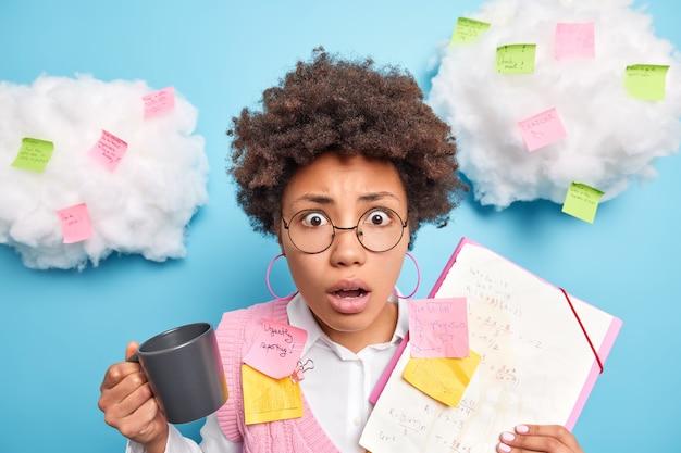 Portret zdumionej kobiety z kręconymi włosami pije kawę zajęta wykonywaniem projektu startowego zawiera folder z papierami otoczonymi naklejkami pocztowymi, aby pamiętać, że wszystko nosi okrągłe okulary w pozach w biurze