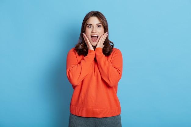 Portret zdumionej zdumionej pięknej kobiety o zdziwionym wyrazie, pozuje pod błękitną ścianą, trzymając dłonie na policzkach, z szeroko otwartymi ustami, ubrana w pomarańczowy sweter.