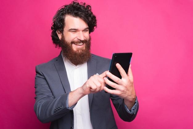 Portret zdumiony brodaty mężczyzna przyczynowy za pomocą tabletu na różowym tle