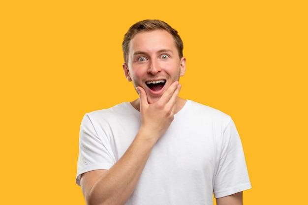 Portret zdumiony mężczyzna. oferta specjalna. podekscytowany facet z ręką na brodzie otwarte usta uśmiechający się na pomarańczowym tle.