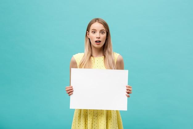 Portret zdumiony młoda blond kobieta trzyma pusty znak z miejsca na kopię na niebieskim tle studio. pokazuje zszokowaną twarz z zaskoczenia.