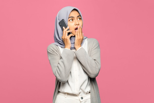 Portret zdumiony młoda kobieta azji rozmawia z przyjaciółmi w telefonie komórkowym