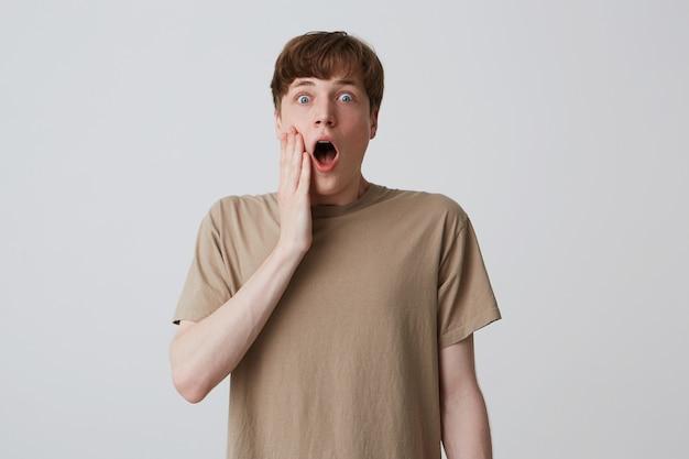 Portret zdumiony przystojny młody człowiek w beżowej koszulce