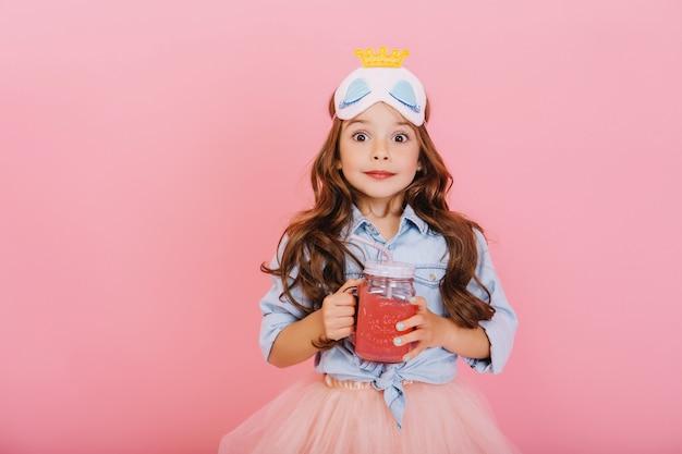 Portret zdumiony radosną dziewczynką trzymając szklankę z sokiem, wyrażając do kamery na białym tle na różowym tle. śmieszne słodkie dziecko w masce księżniczki świętuje, zabawy w szczęśliwe dzieciństwo