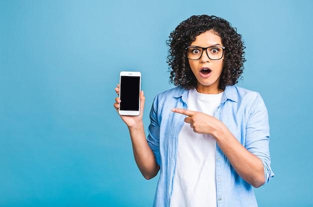 Portret zdumiony, zszokowany młody afroamerykanin czarna kobieta trzyma pusty ekran telefonu komórkowego na białym tle na niebieskim tle.