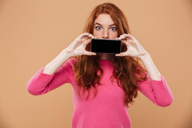 Portret zdziwiona atrakcyjna rudzielec dziewczyna pokazuje smartphone