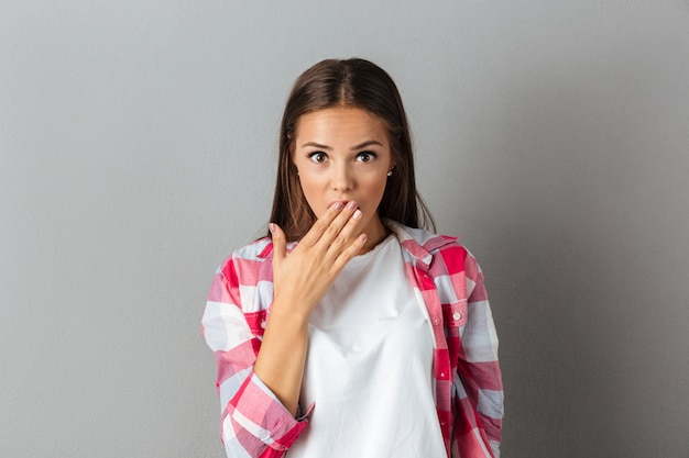 Portret zdziwiona brunetki kobieta w szkockiej kraty koszula