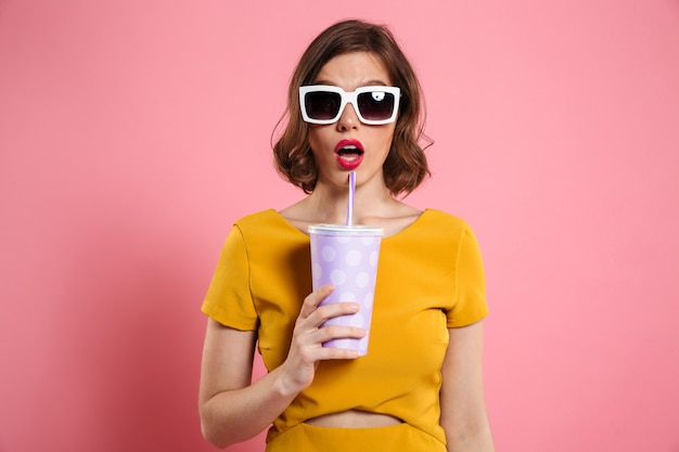 Portret zdziwiona dziewczyna trzyma filiżankę w okularach przeciwsłonecznych